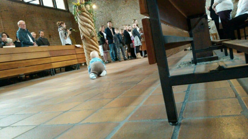 Baby krabbelt bei Taufe in Kirche umher