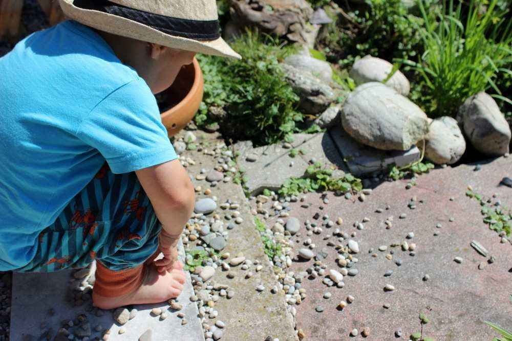 Kleiner Junge spielt ruhig mit Steine