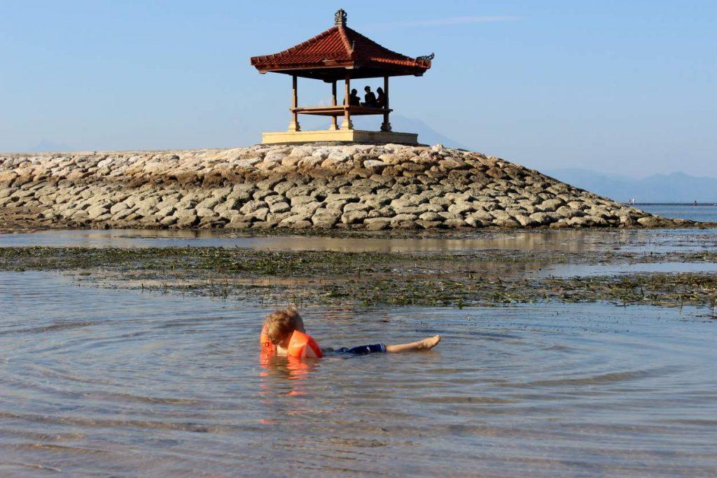 Kleiner Junge badet im flachen Meer in Sanur auf Insel Bali
