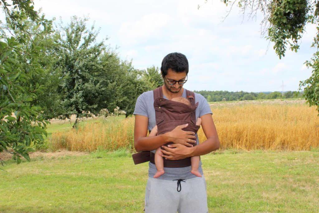 Vater trägt Neugeborenes Baby in Marsupi Breeze Babytrage